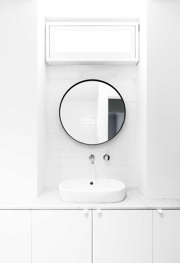 """**Bathroom** Without natural light, the architects had to work hard to make the bathrooms shine. A faux window above the mirror works to great effect. """"Often, people come out puzzled, and they sort of say, 'where does that window go?',"""" says Lesley with a laugh."""