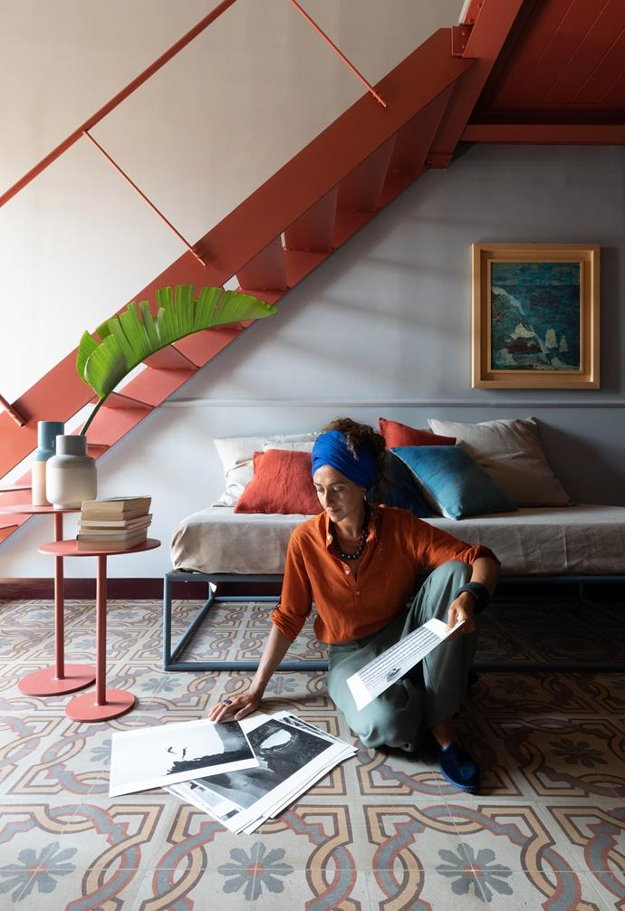 Homeowner Gaia Trapani relaxes in her living space, which connects to the kitchen and mezzanine. The coffee tables and sofa are custom made from lacquered tubular iron and furnished with indigo blue cushions. A collage by Gianni Pennisi hangs on the wall.