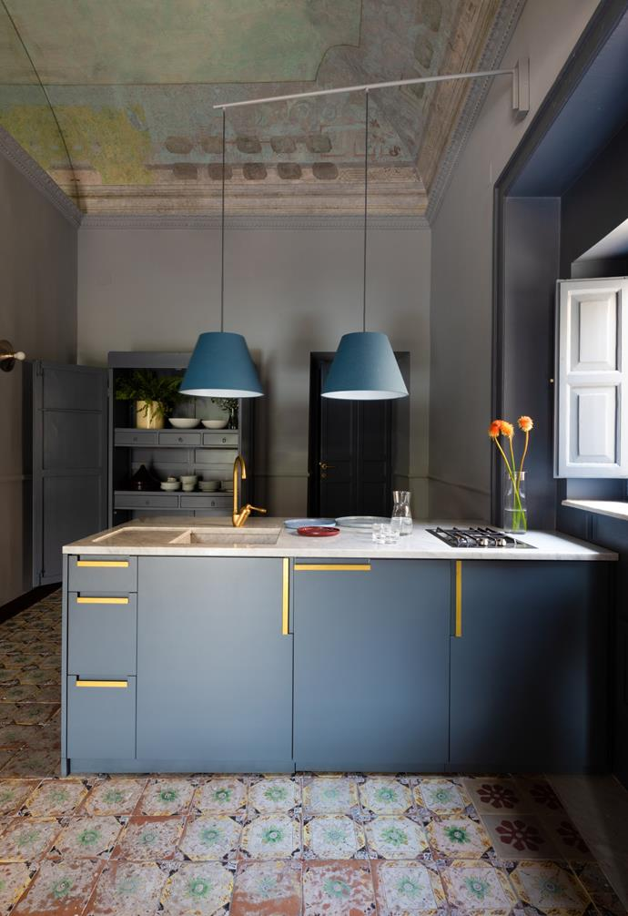 The kitchen forms part of an open-plan space with the living area and showcases the original majolica floor tiles. The Carrara marble benchtop and brass handles elevate the blue-lacquered cabinetry. Rilux Mondoluce pendant lamps zone the area.