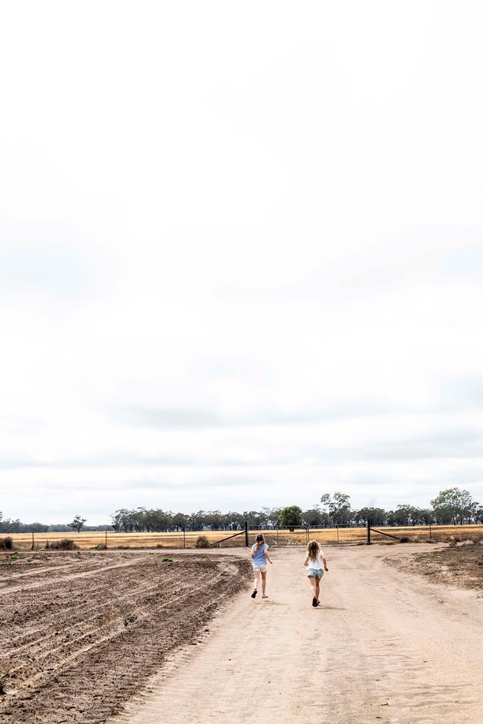 The girls run between the paddocks.