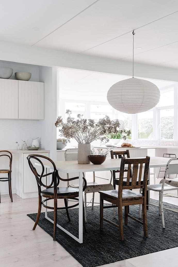 The table, by Unearthed Garden, is a white powder-coated metal frame inlaid with white-washed plywood. The chairs are original bentwood mixed with white chairs from Scout House and vintage finds.