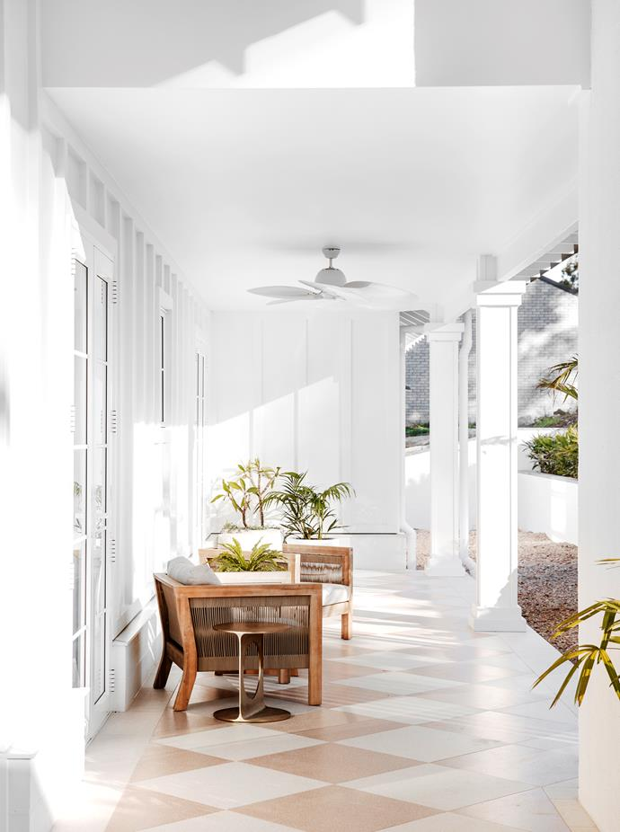 Stairs lead down from the driveway to the front door where a whole glamorous world awaits. Chequerboard terrazzo-look Paddington tiles in white and peach, TileCloud. Armchairs, coffee table, occasional table and planters, all Freedom. Exterior cladding, James Hardie.