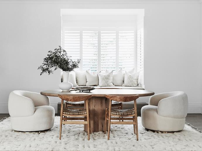 Custom dining table, The Wood Room. Porto Tanduk dining chairs and Munich swivel tub chairs, Oz Design Furniture. Daybed cushions from Florence Broadhurst Fabrics. White vase on table, McMullin & Co. Camilla rug, Miss Amara. Shutters, Luxaflex Window Fashions.