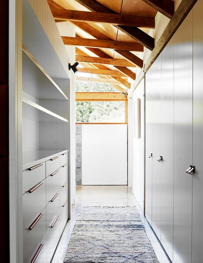 """A moroccan runner from Cadrys and leather handles and pulls from MadeMeasure bring character and warmth to the minimalist custom joinery in the wardrobe of this new [barn-style home in the Byron Bay hinterland](https://www.homestolove.com.au/barn-home-byron-bay-hinterland-22459