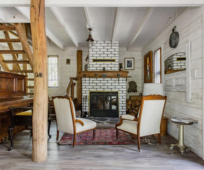 The white washed fireplace is the focal point of the cabin's cosy living room.