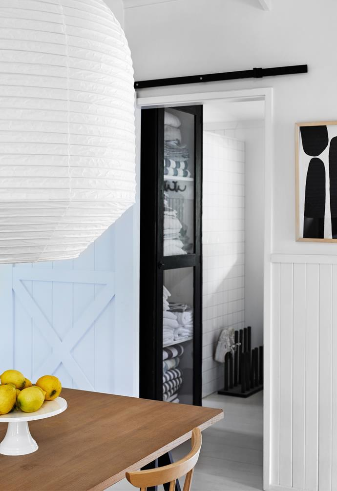 A barn door from Bunnings painted Dulux 'Ballet Blue' opens to the new mudroom area, with its shoe stand from eBay and linen cabinet from Scout House. The artwork is by Anne Miller.