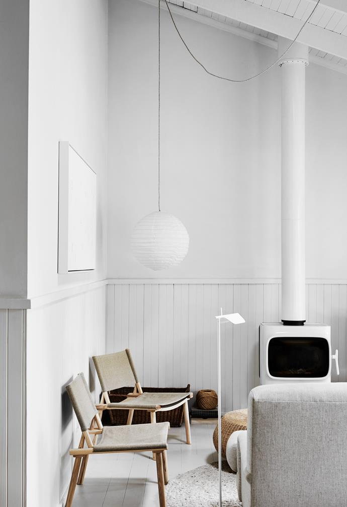 """Eager to make use of her new weekender in the Mornington Peninsula, owner and interior designer Carole Whiting gave the place a quick refresh. """"I painted the floorboards Dulux 'Grey Pebble' halfstrength,"""" she tells. """"It softens the look of the house."""" She replaced the old fireplace with a white Jotul model from Wignells and added Nikari chairs from KFive + Kinnarps, a Scout House sofa from eBay, a Salsa Jamaica rug from Halcyon Lake, Euroluce 'Tab' floor light and Society Inc pendant. The artwork titled Rain is by Phoebe Halpin."""