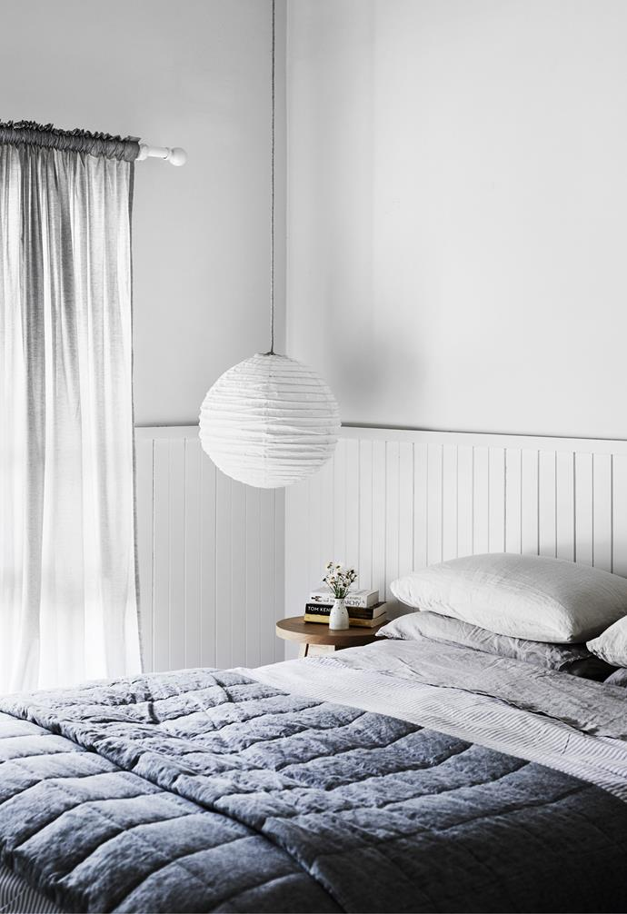 Soft greys and blues in the Bemboka bedlinen and Ikea curtains make the master bedroom a truly restful space. An Agostino & Brown 'Fig' bedside table is piled with holiday reads, and a Sibella Court pendant casts a warm glow over the room.