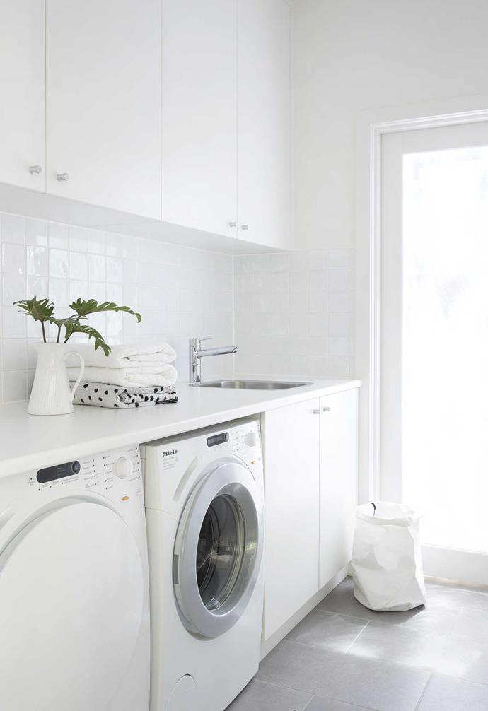 """**Laundry** It's all about white in this crisp zone, from the glossy tiles on the splashback to the paper basket from [Country Road](https://www.countryroad.com.au/