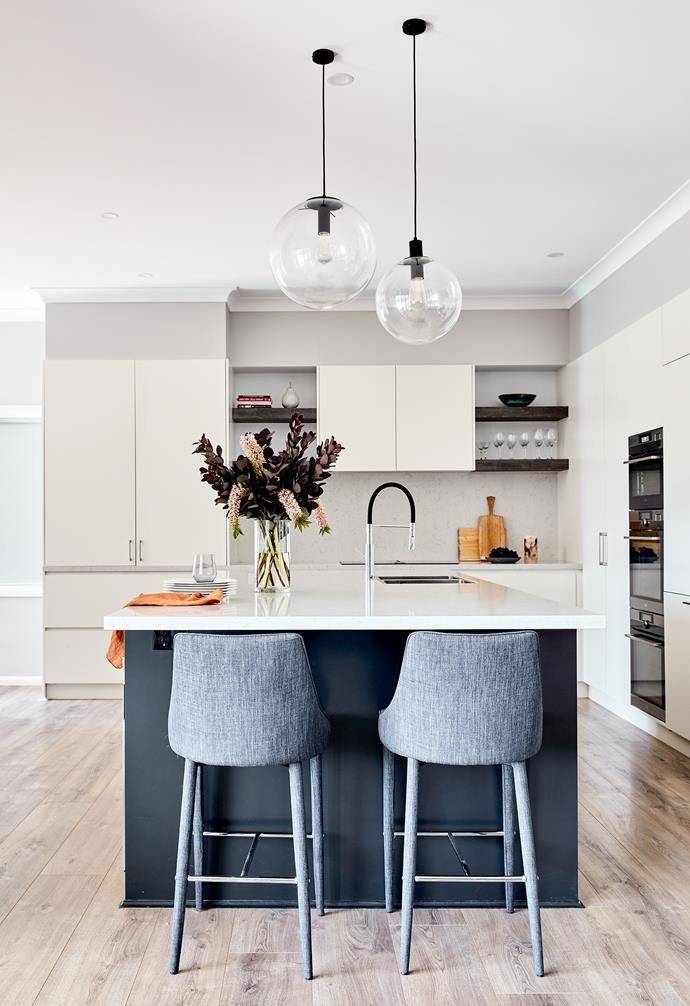 """""""Clean lines and a fresh feel were musts for the couple's new kitchen, but they were worried a simple white kitchen might not create enough wow-factor,"""" says designer Pat Clarke from Dezign Kitchens. Bar stools from Temple & Webster add a masculine touch that picks up on the flooring tones."""