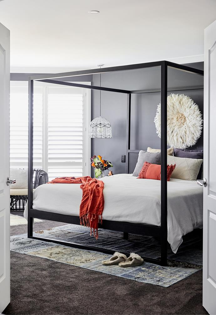 """""""I believe in creating focal points in a room – pick the players,"""" says interior designer Sarah. """"You need to have the drama, but not go too over the top."""" In the couple's striking suite, the 'Strand' four-poster bed by Uniqwa commands attention, in unison with the Bamileke feather headdress by Safari Fusion over the bedhead. The Adairs cushion and throw in Rust inject spice while the Temple & Webster rug adds a splash of cool underfoot."""