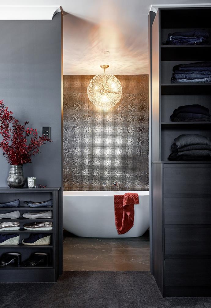 """""""I love the layout of luxury hotel bathrooms and didn't want an open concept space for our ensuite,"""" says Robyn. The shower and toilet are hidden behind dark frosted doors, allowing the resort style Industrie Tapware bath, and the statement pendant by Cafe Lighting, to be the focal point of the room. Shimmering mosaics across the wall reflect light and increase the room's sense of opulence."""