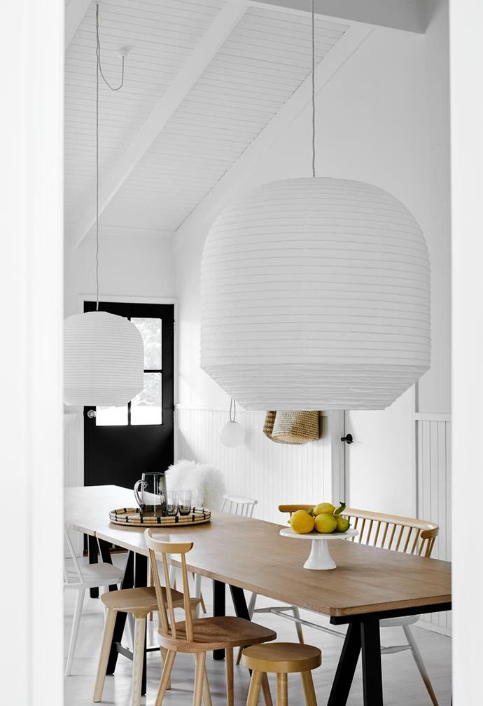"""Two oversized Twentytwentyone 'Hotaru' lamps from Space, in luxurious linen, are suspended over the dining table in this [cosy monochrome cottage in rural Victoria](https://www.homestolove.com.au/cosy-modern-cottage-victoria-22505