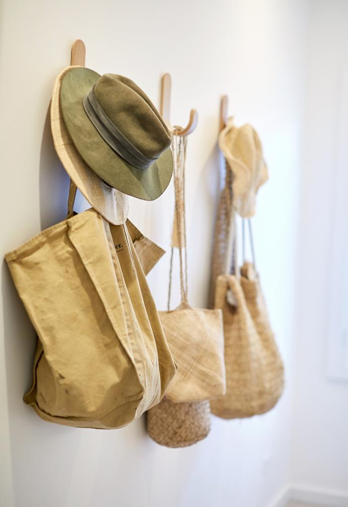 Timber wall hooks near the front door provide extra wall storage for bags and hats for the busy family.