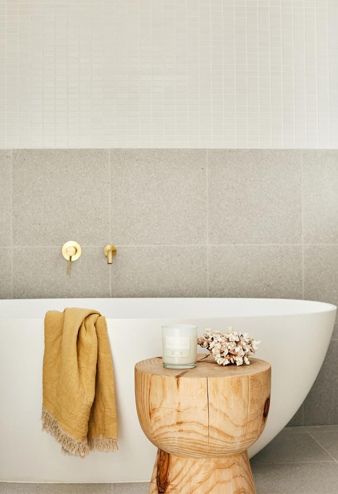 Gold brass hardware, a timber stool and a freestanding bath create a calm main bathroom.