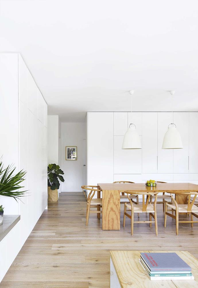 **Open-plan living** This expansive area is the centre of family life in Rachel and Brad's apartment on Sydney's Northern Beaches. The minimalistic look is given warmth with a tactile mix  of timber and concrete. In the living zone, the painted brick wall contrasts with the sleek cabinetry.