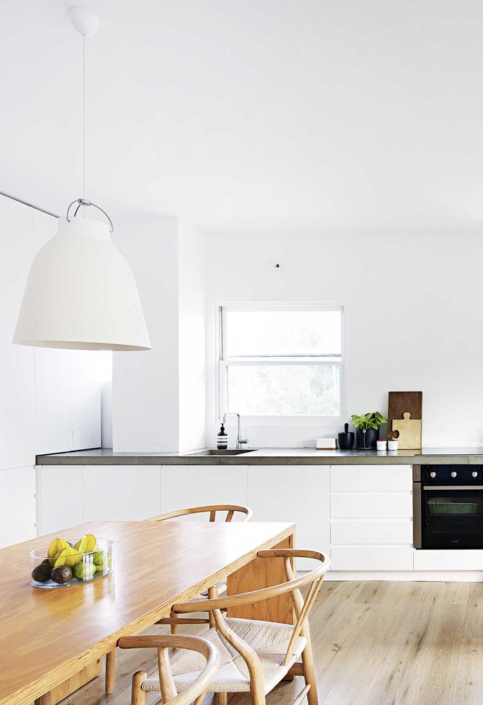 **Open-plan living** The high ceilings are enhanced with industrial-style Lightyears 'Caravaggio P3' lights from Cult that hang above a beloved table and Hans Wegner 'Wishbone' chairs. The couple opted for a more traditional dining setup in the open-plan space.