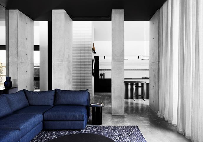 Alix sofa, designed by Marcus Balscheit-Balmain, and Sphinx artsilk-wool rug, both from Surround. Inax 'Sairin' wall tiles, Artedomus. HC28 'Bold' side table, Domo. Off-form concrete columns and steel wall treatments, all custom.