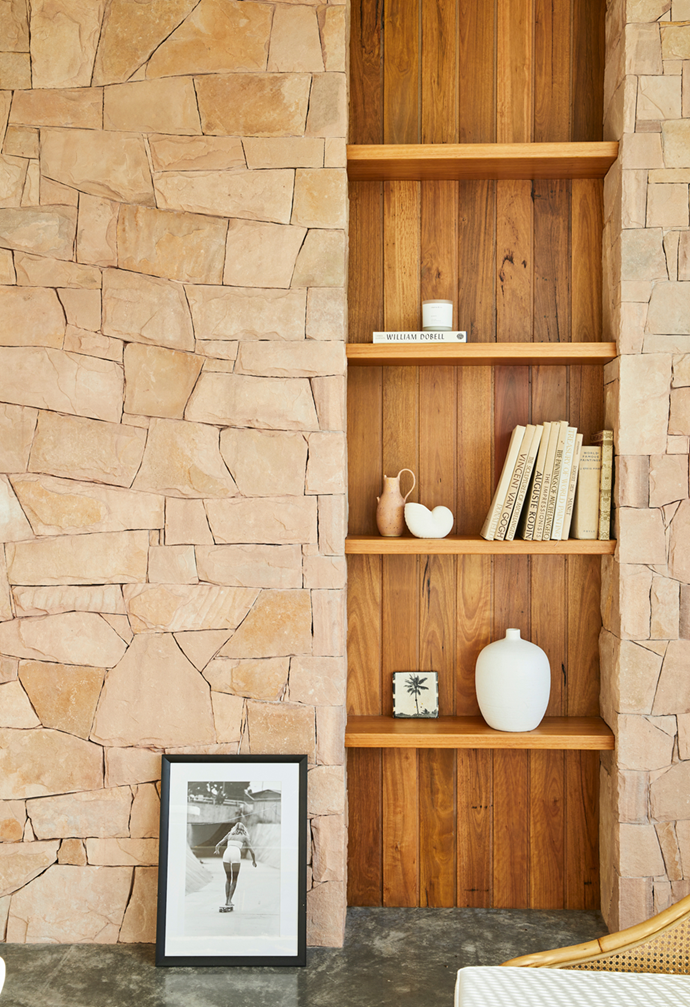 """A timber bookcase is built into the stone-clad wall, which """"was our nod to the mid-century architecture,"""" said the owner of this [sprawling sunlit new-build](https://www.homestolove.com.au/new-build-byron-bay-hinterland-22186
