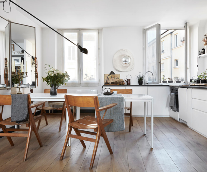 """Timber furniture, craft items and pot plants add warmth to the newly installed kitchen in this [timeless apartment with a tonal Parisian palette](https://www.homestolove.com.au/tonal-timeless-apartment-paris-22359