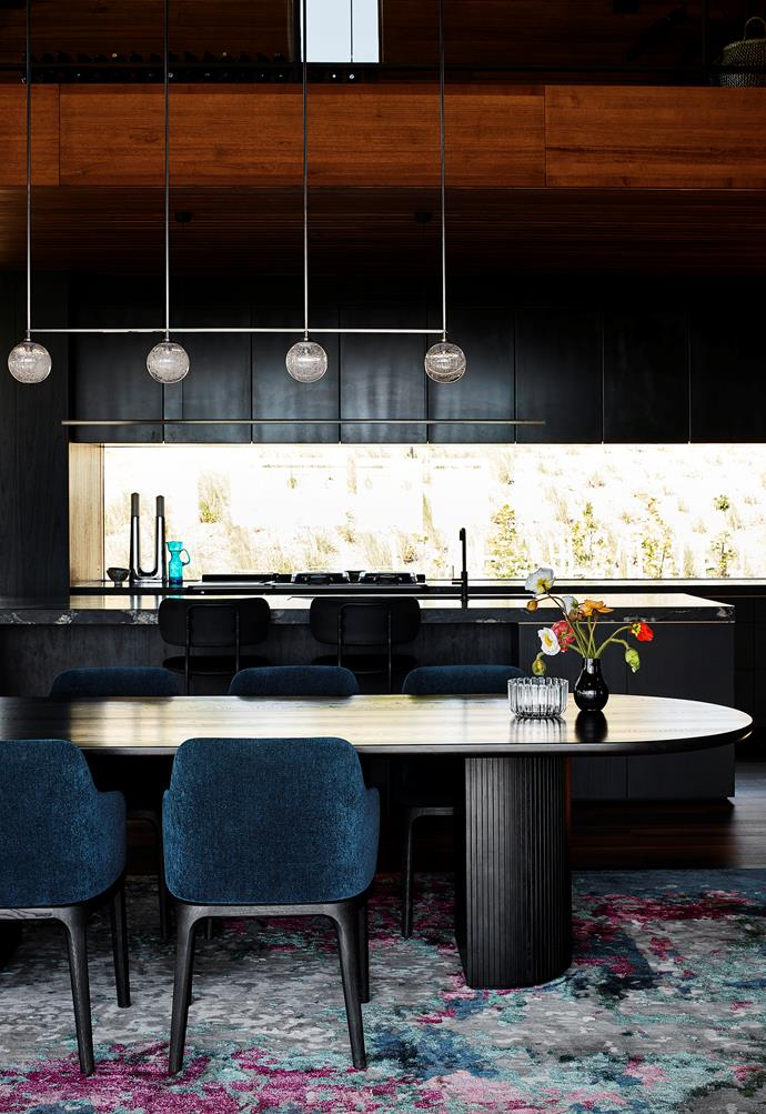 A bronze-finish Articolo 'Fizi' four-ball pendant light illuminates the Gubi 'Moon' oak table from In Good Company with Poliform 'Grace' armchairs. 'Memories' rug from RC+D. Joinery by Fineform in black-stained Tasmanian oak with upper cabinets of blackened mild steel with an OX finish. Gubi 'Coco' stools from In Good Company at the kitchen island.