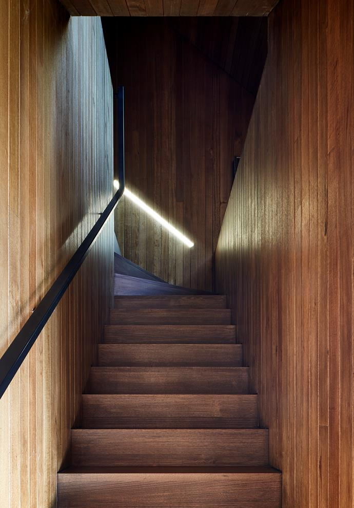 A shaft of sunlight from the skylight pierces the stairwell, which leads to the study and guest suite, in Tasmanian oak from Abelwood with a steel balustrade.