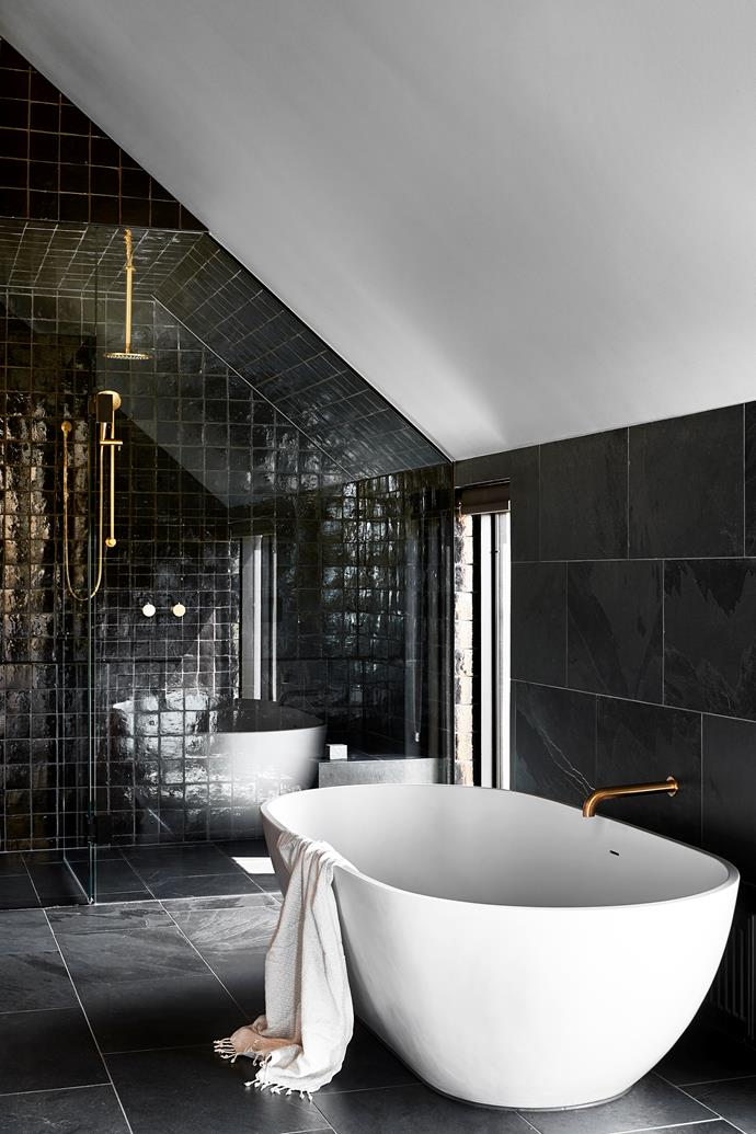 'Justina' bath by Stonebaths in the main bathroom. 'Eastbourne' shower mixer and 'Icon' wall spout, shower rose and hand shower, all in Urban Brass from Astra Walker. 'Cotto' glazed wall tiles and 'Abyss' split-stone floor tiles, all from Eco Outdoor.