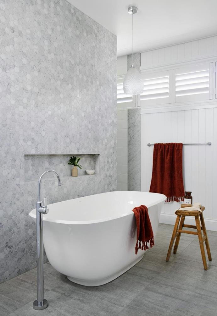 """""""I'm a real bath person and loved this one as soon as I tried it. It's  beautifully deep so you can completely submerge,"""" said Leanne. A Victoria + Albert 'Amiata' bath and Brodware 'Winslow' mixer forms the central feature and is positioned to be admired from the main bedroom. The divider wall is adorned in hexagonal Carrara marble mosaics from 3D Stone and comes with a handy niche. 'Paros' towels in Mahogany from Aura Home offer a splash of colour that can be changed seasonally, and plantation shutters from Decor Blinds allow natural light to be adjusted as desired."""