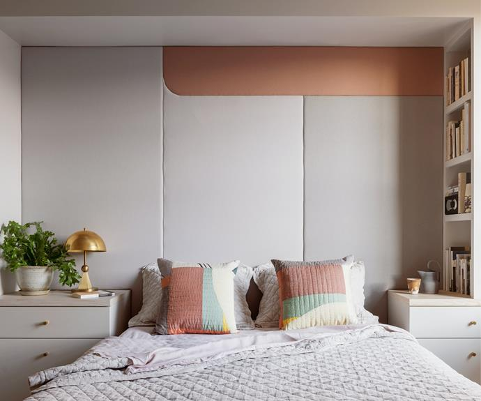 A custom-designed padded wall made by Revive Upholstery helps dampen the acoustics in the bedroom, enhancing sleep. A golden bedside lamp by Michele Varian sits on the built-in bedside table. The throw cushions are from Thompson Street Studios.