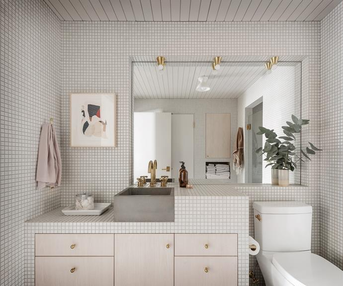 Gold accents, including light fixtures by Anastassiades and Waterworks tapware, add personality to the bathroom. The custom sink is by Cement Elegance.