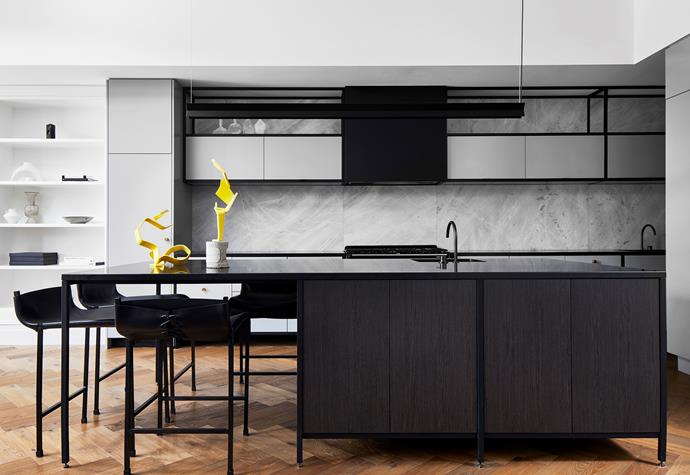 Strong black tones highlight the kitchen and include Zimbabwe Black granite for the benchtops and island bench from Gladstone Granite, 'Chair No.1' iron and buffalo leather chairs by J.M. Szymanski from 1stdibs, Vola tapware in brushed black chrome and an e15 'Span' pendant light from Living Edge. Elba marble splashback from Artedomus. Yellow sculptures by Basil Papoutsidis from James Makin Gallery.
