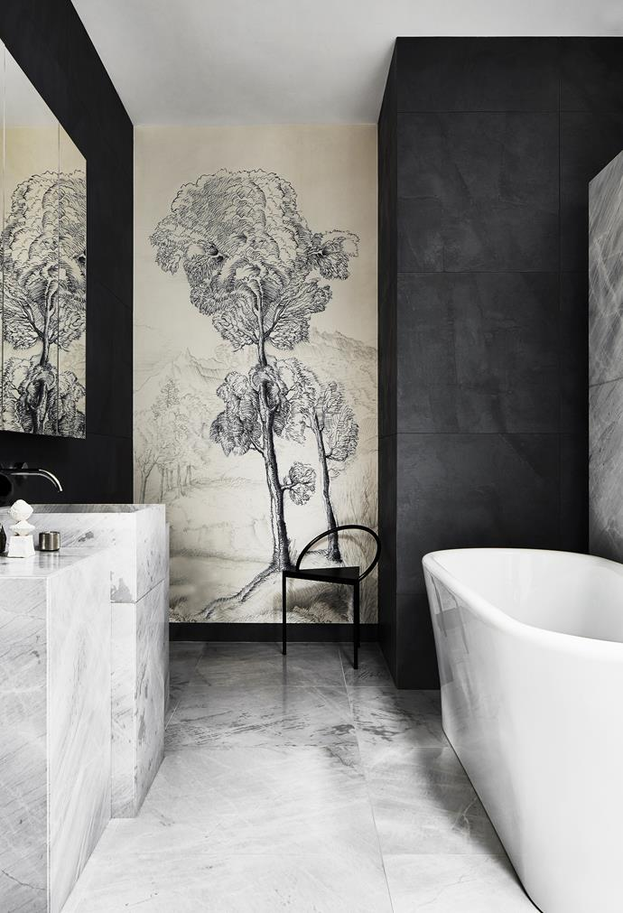 The Wall&decò wallpaper in the master ensuite features a tree motif. The pattern ties in with sculptures that Liz commissioned in the courtyard, which have an arboreal form. 'Etruscan' bath from Albion Bath Company. Elba marble for the floor and vanity from Artedomus. 'Triangolo' steel chair from Frama.