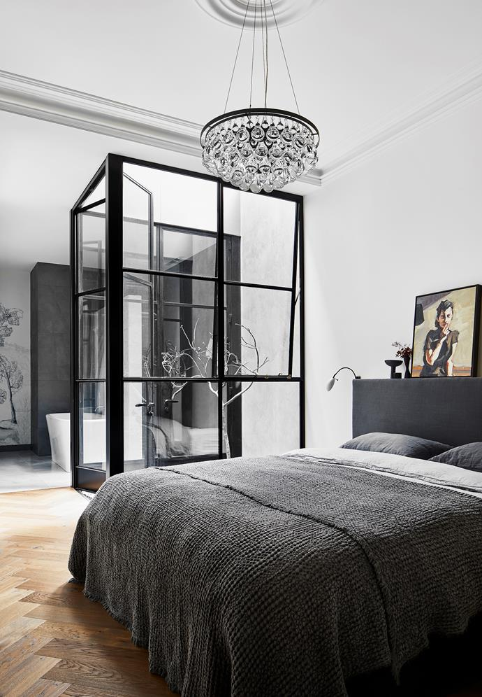 """""""Period buildings are generally dark and gloomy,"""" says architect Nicholas Murray. """"We introduced large steel-framed windows to open up the traditional spaces, such as the master bedroom."""" 'Arctic Pear' chandelier and 'Scorpion' wall light from Ochre. Custom bed designed by Liz Hall. Bed linen and throw from Hale Mercantile Co. Sculpture by Zoe Amor. Artwork by Robert Malherbe from James Makin Gallery."""
