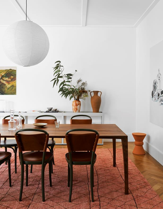 The dining area has a walnut table by Mads Johansen with Gemla chairs from Great Dane and a 'Segovia' rug from Robyn Cosgrove, all under an Akari '75A' pendant light by Isamu Noguchi. Baxter 'Phoenix' stool from Criteria. Artworks by John Papas (left) and Julian Meagher. Glassware on table from Great Dane. Vessels from The DEA Store, Great Dane and McMullin & Co.