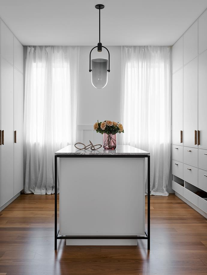 The walk-in robe has custom drawers by Arent&Pyke. 'Arc Well' pendant light by Allied Maker. Sculpture from Studio Cavit and vase from Spence & Lyda.