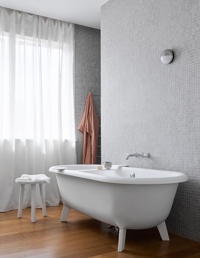 The master bathroom has an Agape 'Ottocento' bathtub from Artedomus, grey stone mosaic tiles from Bisanna. Tapware and accessories from Astra Walker. Stool, bathrobe and caddy from Oliver Thom.
