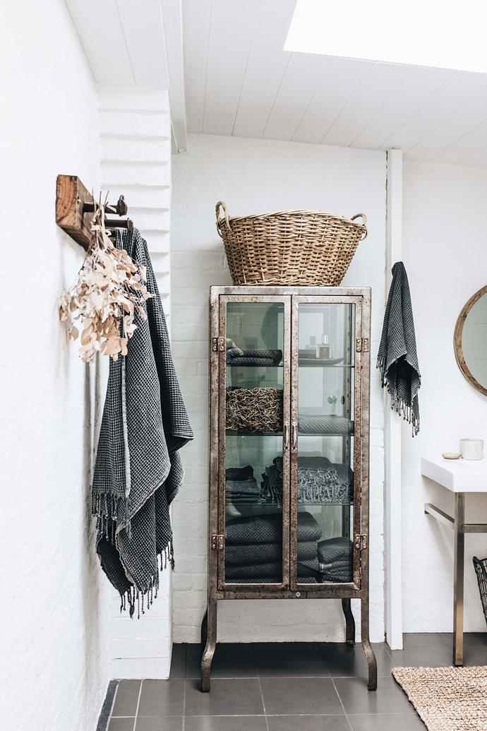A metal cabinet gives the bathroom a touch of vintage style.