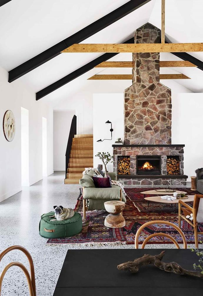 The cathedral ceiling in the 'great room' of this [cosy country farmhouse with modern interiors](https://www.homestolove.com.au/country-farmhouse-17468) pairs a tonal mix of stone, timber, black and white creates an open and inviting feel.