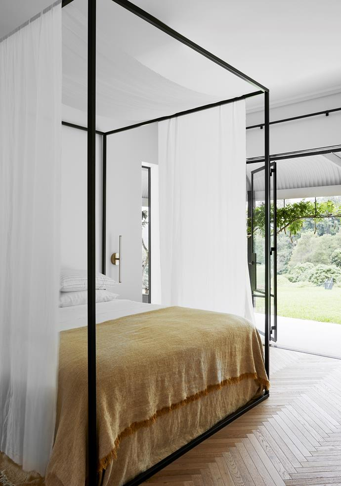 The master bedroom opens to the neighbouring valley and descends to the pool. Bed from Pond with Millar & More bed linen. Wall sconce from Lighting Collective.