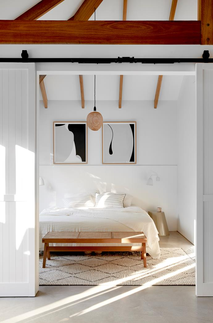 Artworks by Caroline Walls hang above a bed dressed with Millar & More bed linen and cushions. Pendant light from Lighting Collective. Beni Ourain rug and Pierre Jeanneret 'Chandigarh' teak bench, both from Tigmi Trading. 'N°005 Fluidity' tumbler from Soft Edge on an 'Arnold Circus' stool by Martino Gamper from Worn Store used as a bedside table. Fritz Hansen 'Caravaggio Read' wall lights by Cecilie Manz from Cult. Tinted concrete floor.