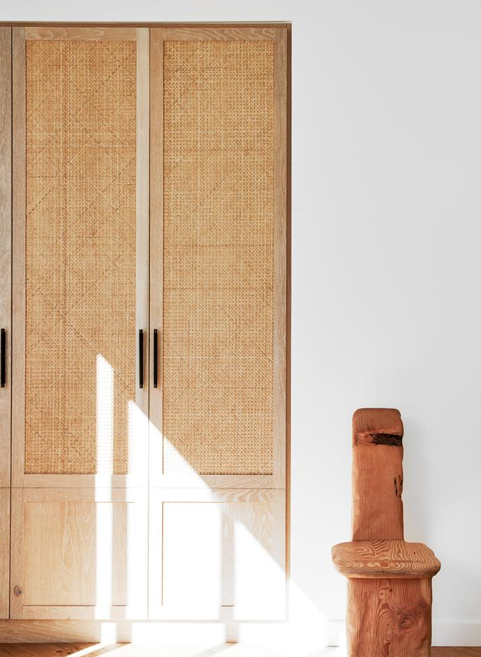 The wardrobe joinery in the guest room was also created by Nailed It Kitchens & Joinery with grasscloth joinery inserts by Wicker Works and MadeMeasure pull handles. Kythe Seat timber chair sculpture by Byron Bay artist Lex Williams from Tigmi Trading.