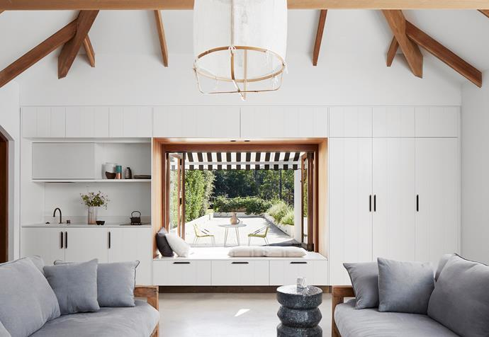 The former garage was converted into a self-contained studio. Ay Illuminate 'Z2' pendant light from Spence & Lyda. 'Judd' sofas and side table from MCM House. Outdoor table and chairs from Tait.