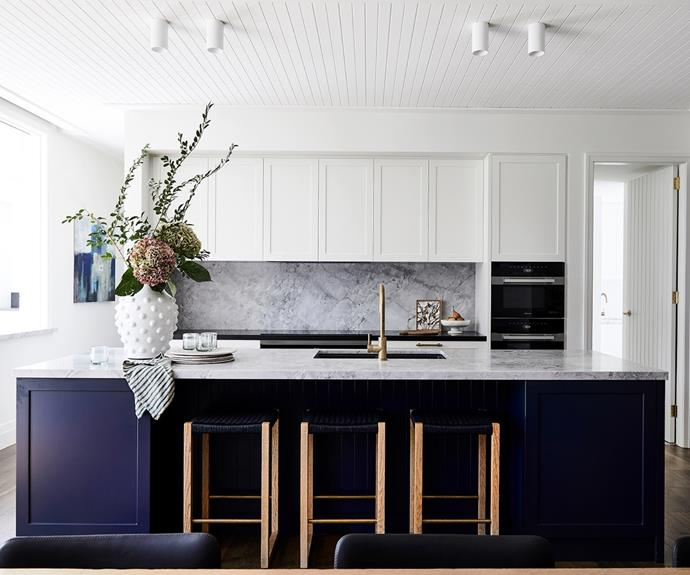 """An oversized island bench topped with honed dolomite stone makes a dark, dramatic statement in Dulux Oolong, with 'Wovenest' bar stools from Modanest tucked underneath. Shaker-style cupboards were custom-made by All Aspects Joinery and painted in Dulux Whisper White. Of her Miele appliances, Nerida is particularly fond of the steam oven. """"The steamer is amazing!"""" she says. """"It's on twice a day and we love it."""" A 'Sovereign' urn from Provincial Home Living housing a beautiful bunch of flowers is among the home's chic styling touches, as is a Katie Wyatt artwork on the rear bench – Nerida found the other artwork about 15 years ago at a market on the Sunshine Coast."""