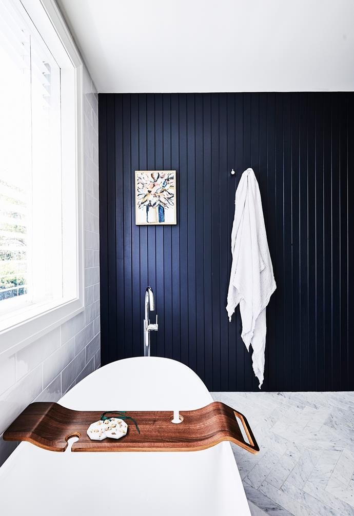 """A [feature wall](https://www.homestolove.com.au/pros-and-cons-of-a-feature-wall-14390 target=""""_blank"""") of VJ panelling references other rooms to create a cohesive design palette."""