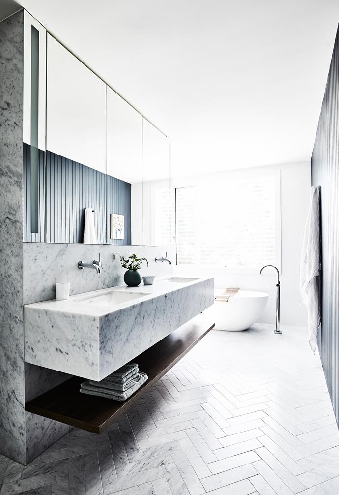"""Encased in Carrara marble, the vanity was custom-made by joiner David Fox of All Aspects Joinery in the ensuite. Nerida designed the ensuite so the shower (around the corner) and bath enjoy the leafy outlook. The mirror has built-in lighting, while exterior Venetian blinds from SCS Blinds ensure privacy and northern- sun control, and Carrara marble herringbone [floor tiles](https://www.homestolove.com.au/bathroom-tile-ideas-5447 target=""""_blank"""") from Teranova amplify the wow factor."""