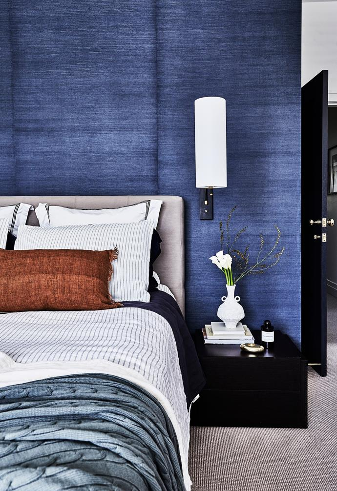 """A wall of navy grasscloth wallpaper from Porter's Paints delivers no-fuss texture and sets the couple's bedroom apart. """"It's a classic, which is why I chose it,"""" says Nerida. """"That was the idea with this house – to select timeless fixtures and finishes that would allow the charm of the old parts to fuse with the new parts."""" A 'Frankfort' wall light from The Montauk Lighting Co is another classic contemporary touch."""