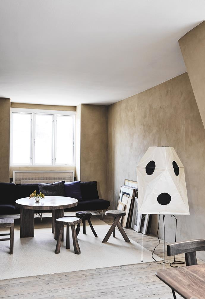 In the living area, a Vitra 'Akari UF3-Q' floor light by Isamu Noguchi does double duty as art and ambient lighting. An Axel Einar Hjorth 'Birka' table in lacquered ash is flanked by an assortment of stools: a round one by Pierre Chapeau; a traditional Finnish sauna stool; and an almost-black, hand-carved French olive tree stool.