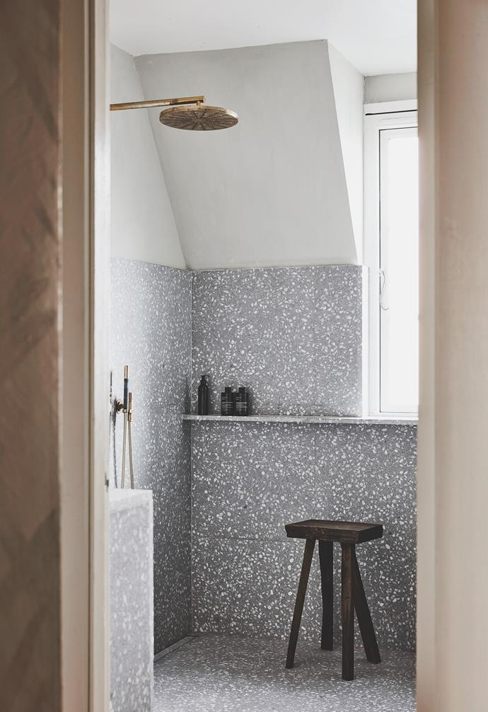 In the bathroom, grey terrazzo is lifted with brass fittings. The stool was designed by Nikolaj for a store in Copenhagen, and the tap is by Vola, the perfect match for the round vintage mirror.