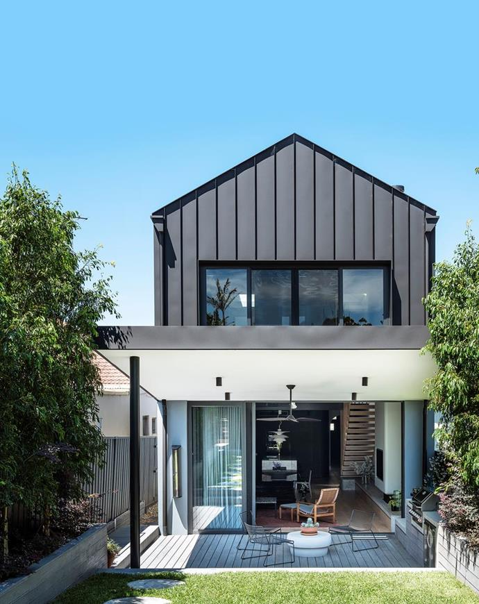 """Colorbond Monument external cladding emphasises the greenery, with decking in grey-stained blackbutt, on the contemporary exterior of this [1940s semi revived into a stylish family home](https://www.homestolove.com.au/1940s-semi-renovation-sydney-22284 target=""""_blank"""")."""