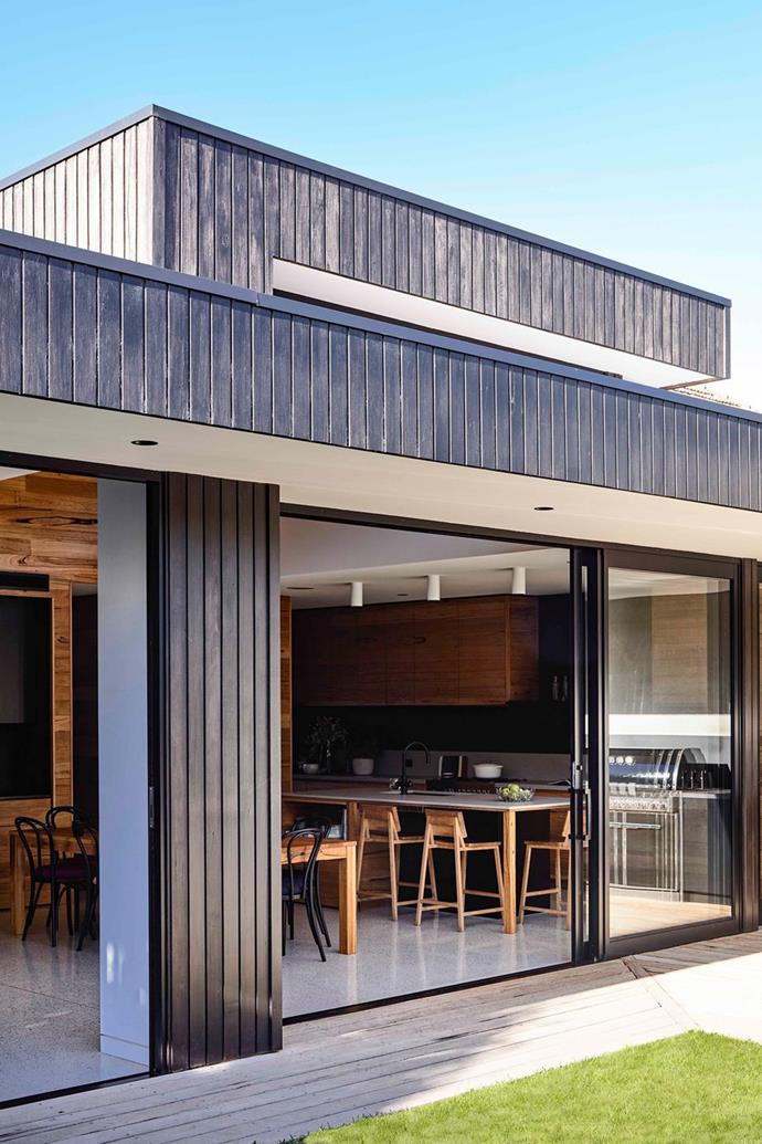 """Floor-to-ceiling powder-coated aluminium-framed glass doors are paired perfectly with the dark timber panelling on the contemporary extension at the rear of this [heritage home in Melbourne](https://www.homestolove.com.au/heritage-home-renovation-melbourne-21673 target=""""_blank"""")."""